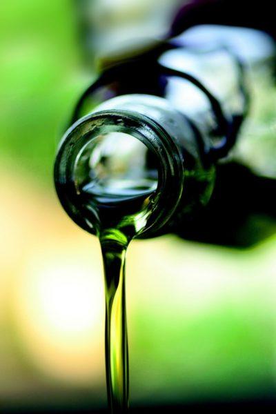 Olijfolie die uit een glazen fles geschonken wordt voor gezond bakken en braden
