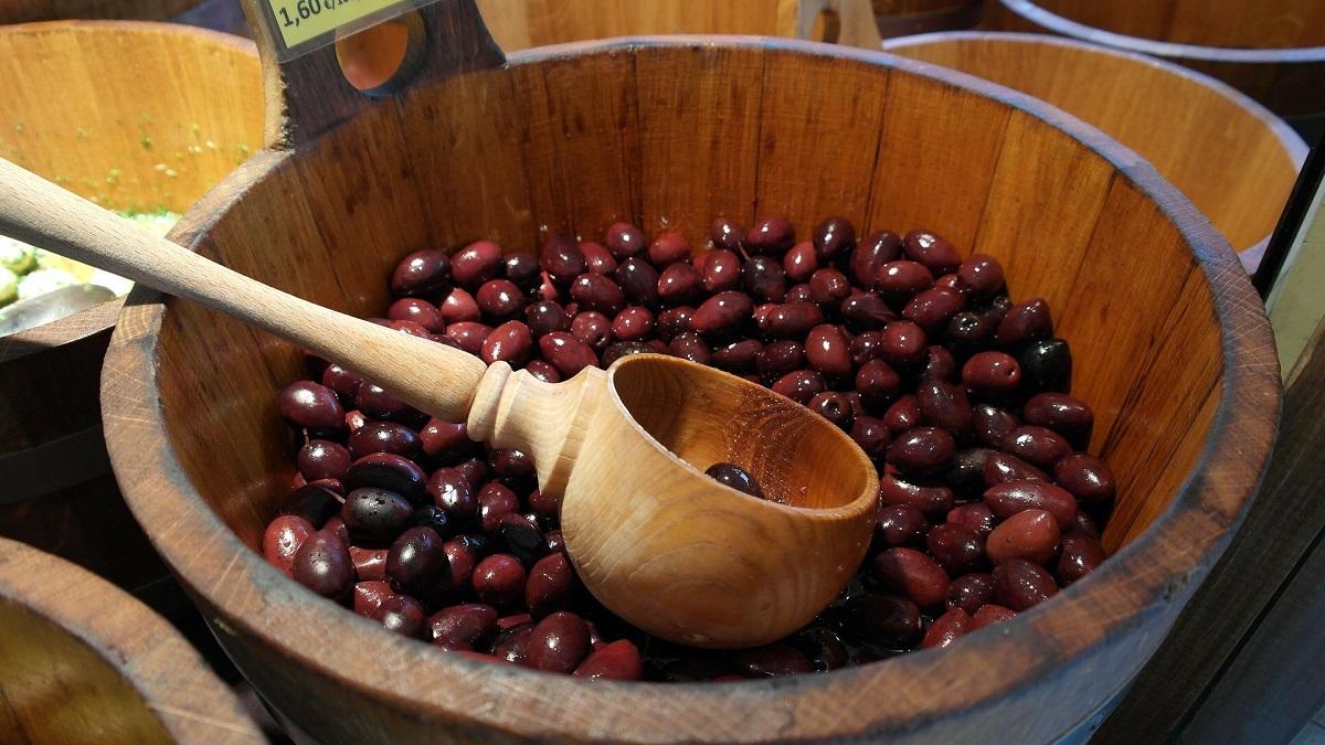Dunkle Oliven im hölzernen Behälter mit hölzernem Löffel
