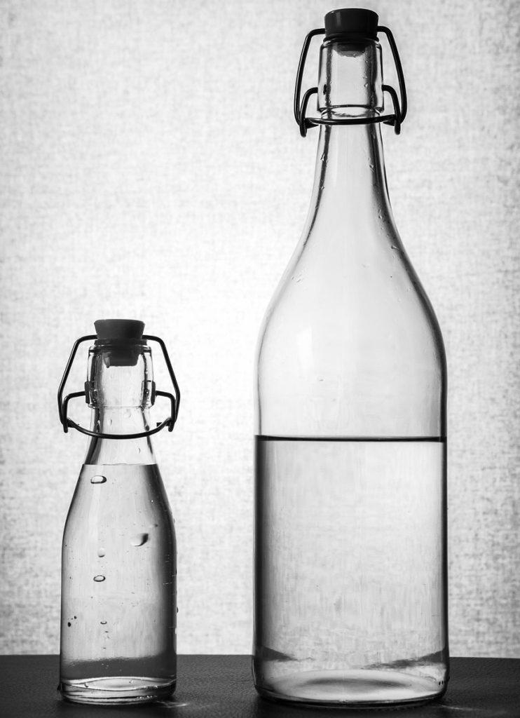 1 kleine und 1 große Glasflasche mit natürlichem Mineralwasser