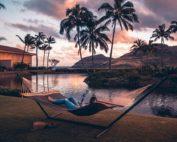 bien-être avec l'huile de coco, se détendre, allongé dans un hamac avec vue sur l'eau et les palmiers