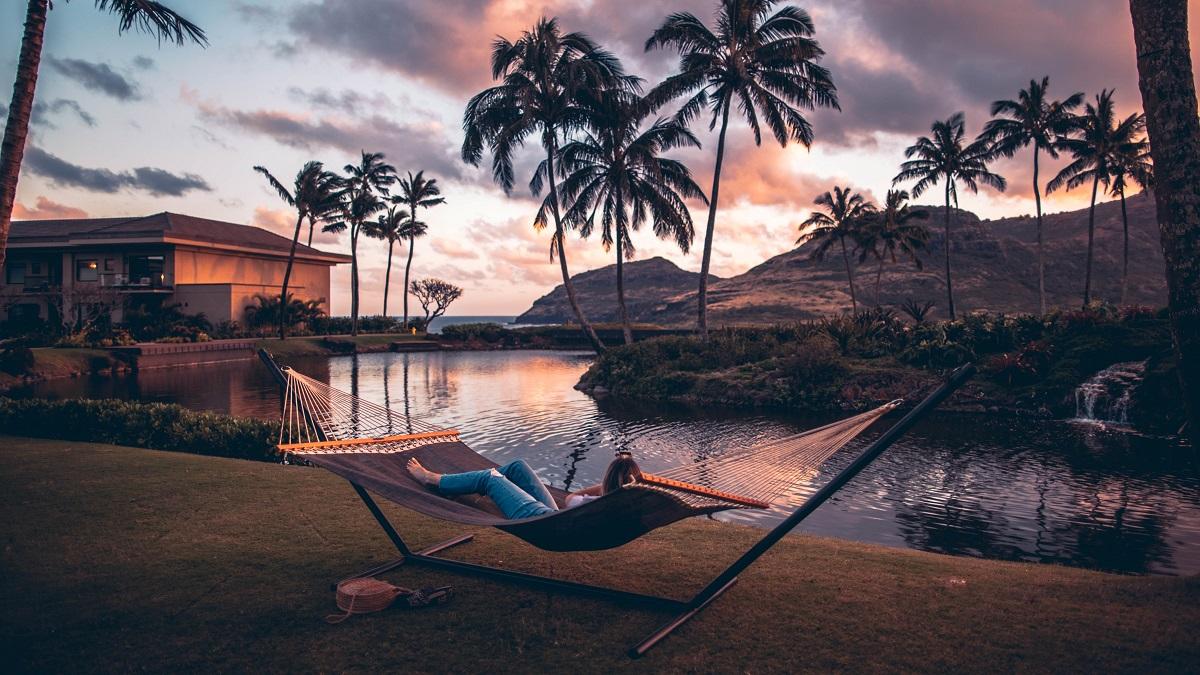 wellness met kokosolie ontspannen liggen in een hangmat met uitzicht over water en palmbomen